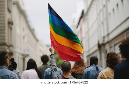 Rear view of people in the pride parade. Group of people on the city street with gay rainbow flag.