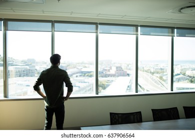 Rear view pf businessman looking through window in meeting room at workplace