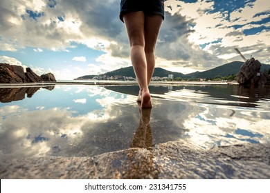 Rear view photo of beautiful slim female legs walking on water surface with reflecting sky