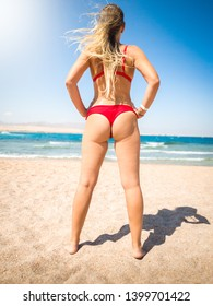 Rear view photo of sexy young woman with long legs and perfect bottom standing on the beach and looking at sea