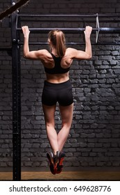Rear view photo of the young fitness woman pulls up on the horizontal bar against brick wall at the cross fit gym.