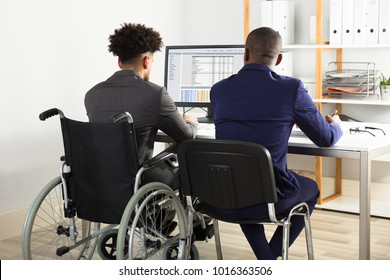 Rear View Of Physically Impaired Businessman With His Partner Working On Computer On Desk