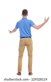 rear view picture of a young casual man welcoming someone with his arm wide open. isolated on a white background