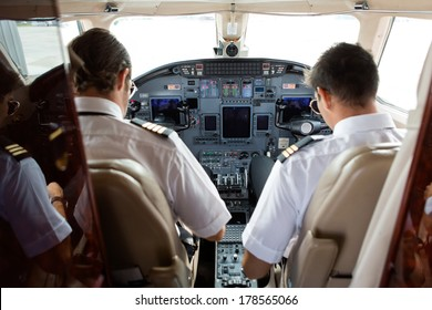 Rear view of pilot and copilot in cockpit of private jet