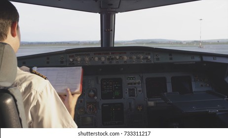 Rear view of pilot operating controls of corporate jet. the pilot checks all the systems. Rear view of pilot and copilot operating controls of corporate jet. Pilot and copilot in commercial plane in