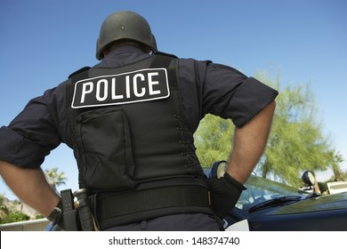 Rear view of policeman in uniform standing against car