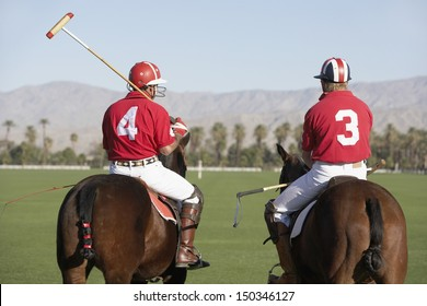 Rear view of polo players holding sticks mounted on horses