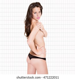 Rear view portrait of an attractive woman wearing black panties, isolated in front of white tiles background