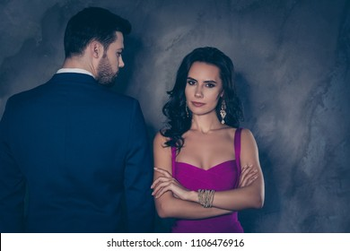 Rear view portrait of brunet business gentleman looking at serious lady with front view in purple outfit with jewelry curly hair seductive decollete holding arms crossed isolated on grey background