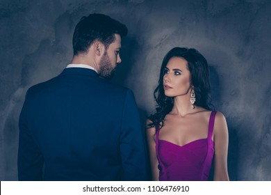 Rear view portrait of brunet gentleman in tuxedo and pretty lady with front view in purple outfit with jewelry earring curls decollete, couple looking at each other isolated on grey background