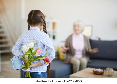 Rear view portrait of cute little girl holding bouquet behind back giving gift to grandmother on Birthday, copy space
