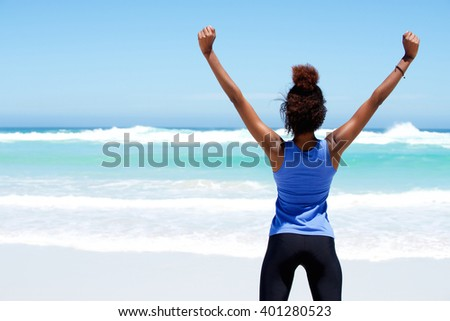 Rear view portrait of fitness woman stretching at beach with her hands raised