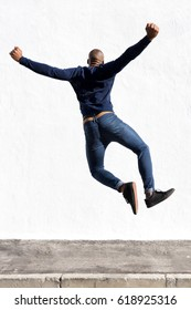 Rear view portrait of young african man jumping in air on sidewalk outdoors
