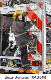 Rear view portrait of young firewoman climbing truck at fire station