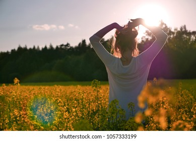 Rear view portrait of young girl standing in colza field with arms raised during warm sunset