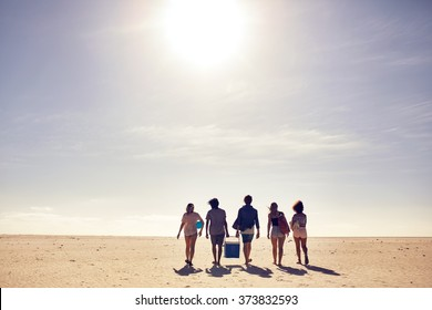 Rear view portrait of young people carrying cooler box walking on the beach. Looking for a spot for party. Friends on beach vacation, on a hot summer day.