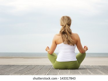 Rear view portrait of a young woman sitting at beach in yoga pose