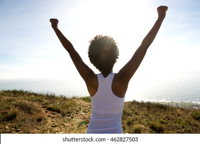Rear view portrait of young woman standing on cliff with her hands raised towards sky and looking at the sea