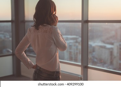 Rear view portrait of young worker speaking using cell phone, looking out the window. Female having business call, busy at her workplace in evening.