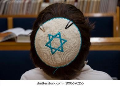 A rear view of praying young man with star of david, magen david, yarmulke