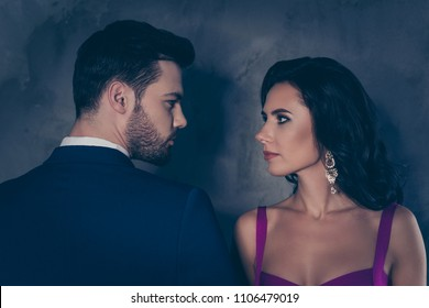 Rear view profile of brunet mr with stubble and pretty charming mrs with jewelry earring curls decollete, naughty spouses looking at each other isolated on grey background
