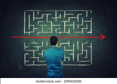 Rear view of a puzzled businessman in front of a blackboard finding a solution to escape from labyrinth. Breaking the rules, as a red line pierce the maze walls.