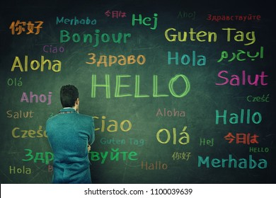 Rear view of a puzzled businessman in front of a huge chalkboard written with the word hallo in different languages and colors. Opportunity for learning many languages for students.