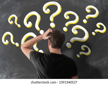 rear view of puzzled man in t-shirt scratching his head in confusion against blackboard filled with question marks