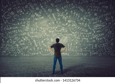 Rear view of puzzled student, hands on hips, stands in front of a huge blackboard try to solve hard mathematics calculation, formula and equations. Project ideas thinking, business planning concept.