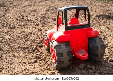 rear view of a red tractor made of plastic, a tractor on a field of dry brown soil