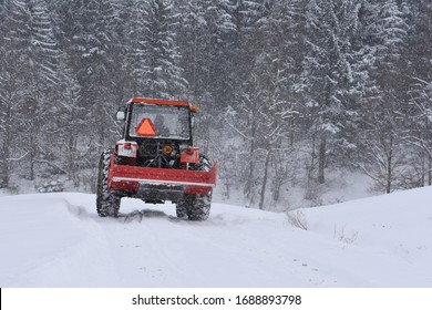 Rear view of red tractor on a snow covered countryroad in misty winter landscape