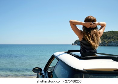 Rear view of relaxed woman on summer travel vacation to the coast leaning out car sunroof towards the sea.