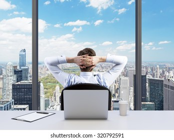 Rear view of the relaxing businessman with crossed hands behind his head, who is looking at the Cntral park. Modern Panoramic office or work place with New York city view.