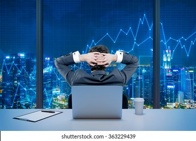 Rear view of a relaxing trader who is sitting in front of a window, laptop behind him. Night New York view. Graphs at the background. A concept of forex trading.