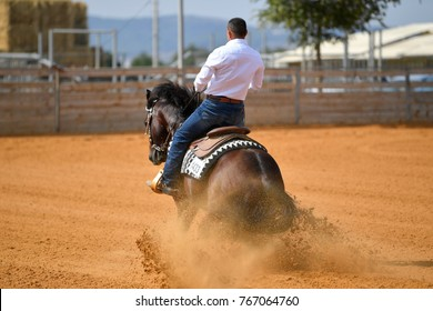 The rear view of a rider in cowboy chaps and boots sliding the horse into the sand