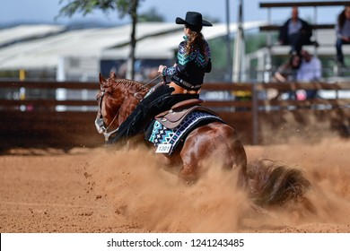 The rear view of a rider in jeans, cowboy chaps and checkered shirt on a reining horse slides to a stop in the red clay an arena.