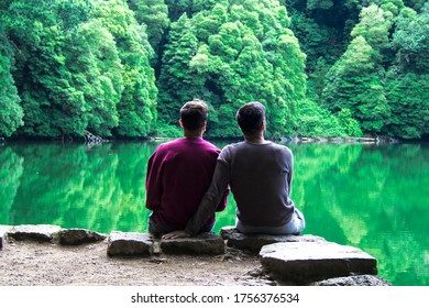rear view of a romantic gay couple sitting in a beautiful landscape with lake and mountains in a calm moment