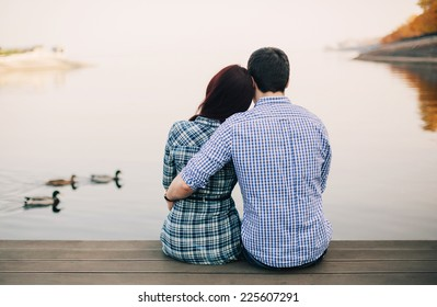 Rear view of a romantic young couple sitting on the river dock in autumn