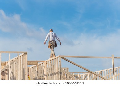 Rear view roofer builder on wooden roof trusses construction. Worker with carpenter tool belt working balancing on roofing. New home site house foundation framing in Irving, Texas, USA