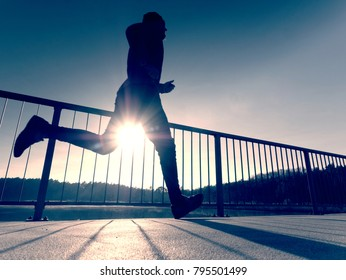 Rear view to runner in blue t-shirt and black leggings  running on bridge. Outdoor exercising on smooth concrete ground on lake bridge. Sun is outlining man body