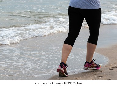 Rear view of a runner is running on the hard sand close to the ocean wearing spandex.