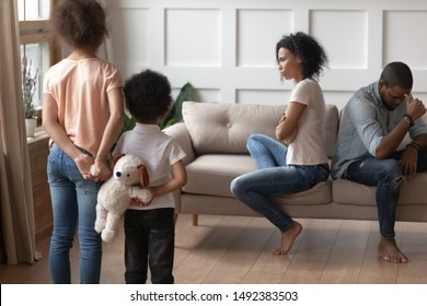 Rear view sad african little son and daughter look at parents in quarrel sit on couch separately from each other, negative influence psychological trauma for children, break up of mom and dad concept