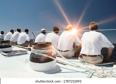 Rear view of sailing crew with lens flare