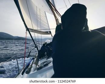 Rear view of sailor sailing on the waving sea. Skipper sailing on the sailboat