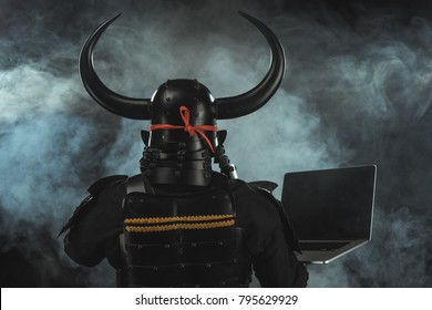 rear view of samurai in traditional armor with laptop on dark background with smoke