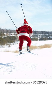 Rear view of Santa Claus jumping on skies