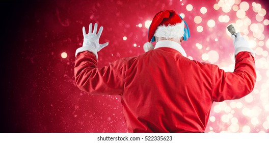 Rear view of Santa Claus listening to music against light design shimmering on red
