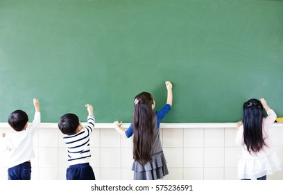 rear view of school students drawing on chalkboard