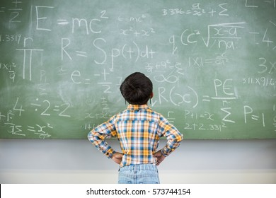 Rear view of schoolboy looking mathematics on chalkboard in classroom at school