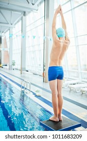 Rear view of schoolboy in swimwear standing on diving board with his arms raised and put together before dive